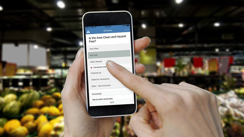 Woman's hands holding smart phone, online shopping application on screen, grocery aisle of a supermarket in the background.