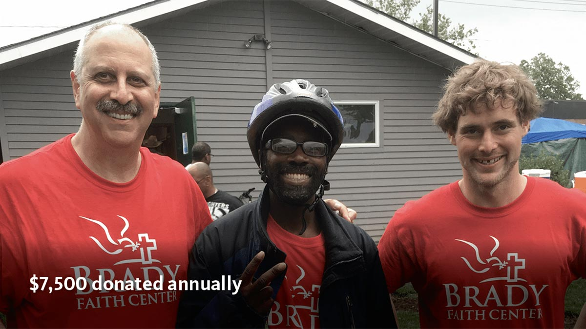 Three men in red t-shirts, smiling