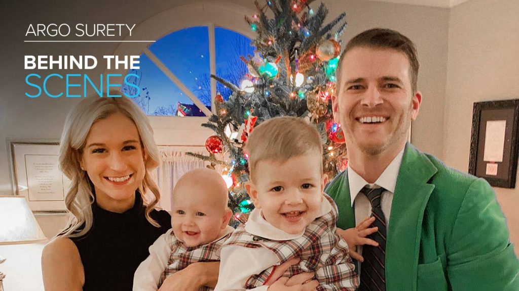 Argo Surety employee Brendan Keating posing with wife and children in front of Christmas tree