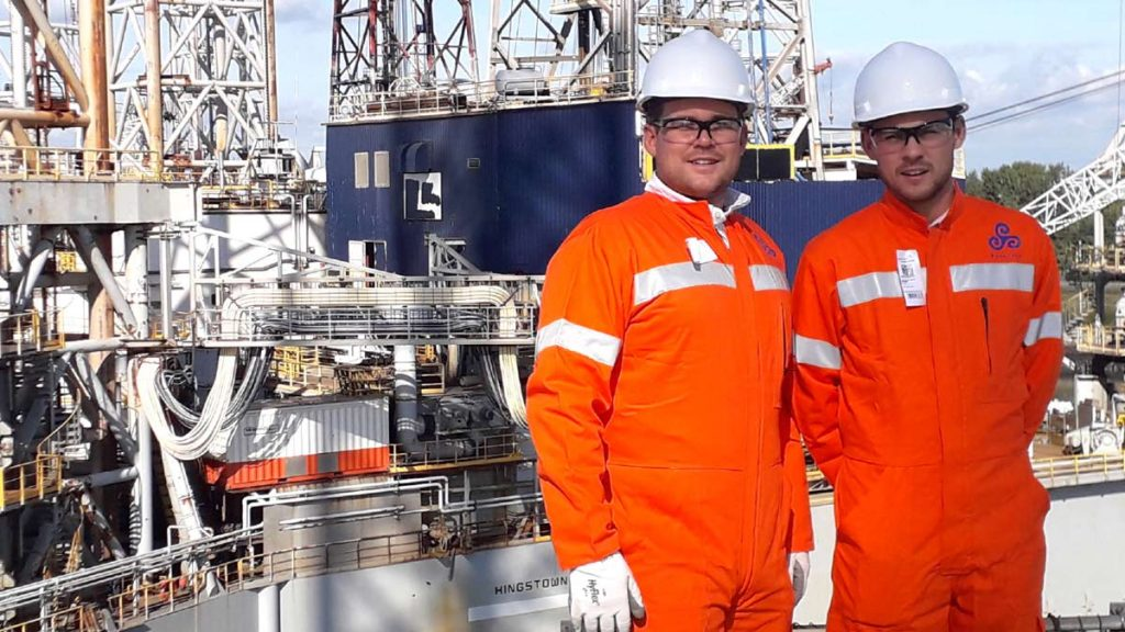 Two employees posing on an offshore rig dressed in protective gear