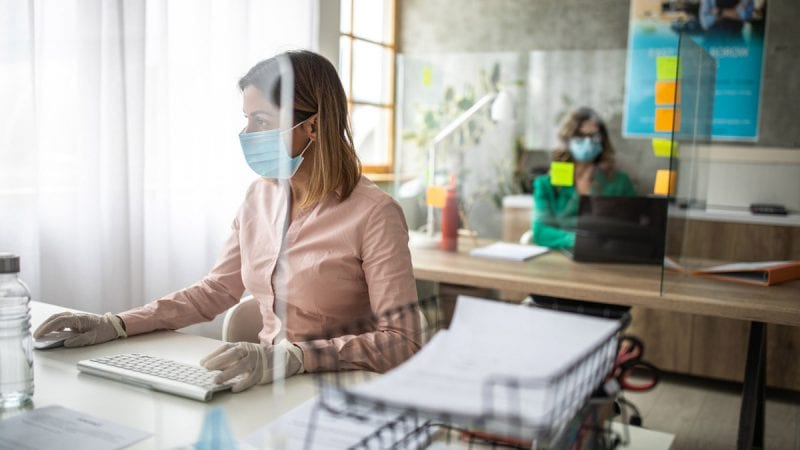 Woman wearing a mask and working in an office