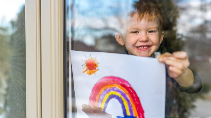 Young toddler smiling in a window showing a rainbow drawing