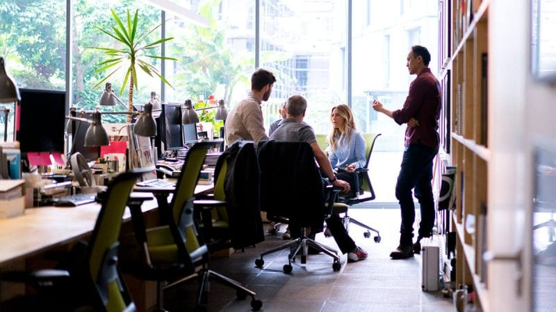 Leaders speaks to a group of professionals in an office setting