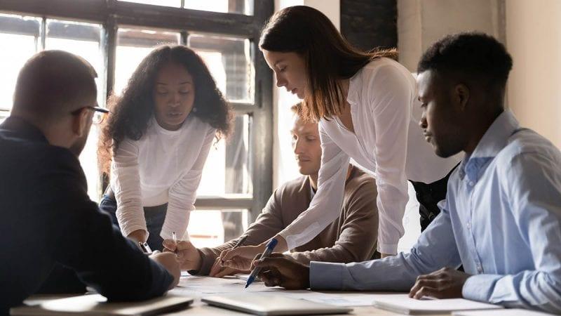 Focused diverse team people discuss corporate paperwork share ideas