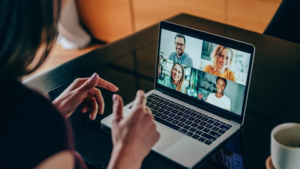 Young woman talking to her friends in video call from home. Multi-ethnic group of people using laptop for a online meeting in video call. Friends having online conversation during quarantine.