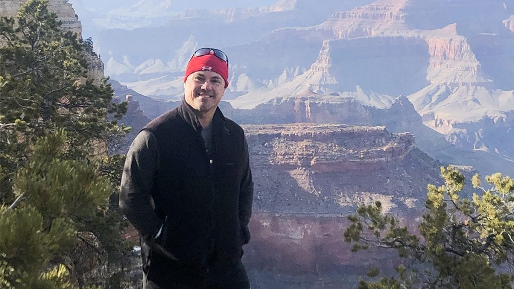 Marcus Morissette standing atop a scenic landscape