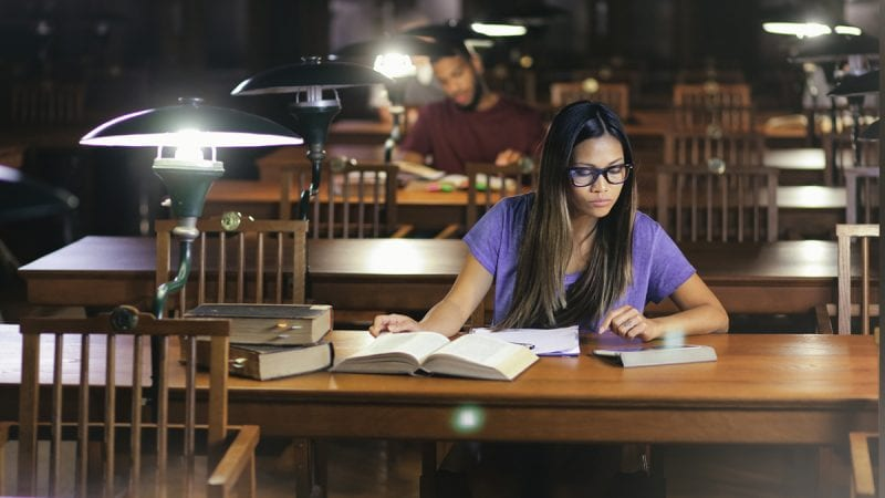 Young college student studying in a dimly-lit library