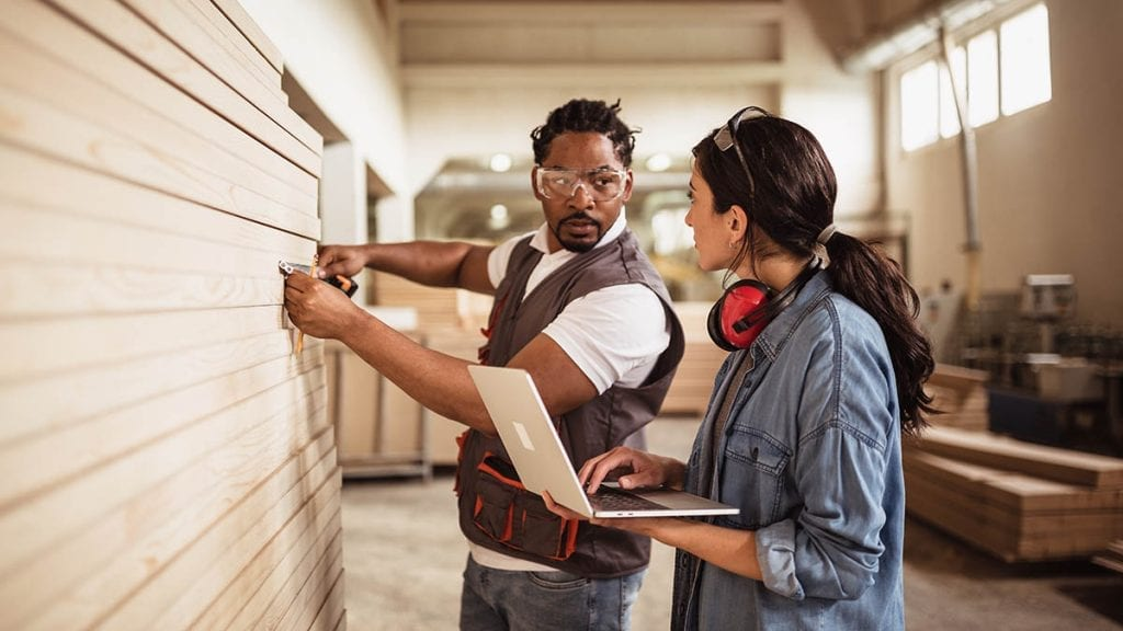Male and female contractor working together on a project, measuring lumber.