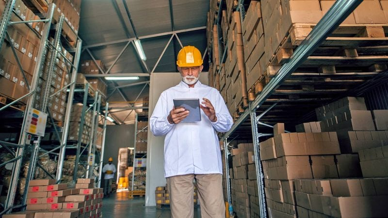 Warehouse employee using mobile device while standing next to a row of boxes