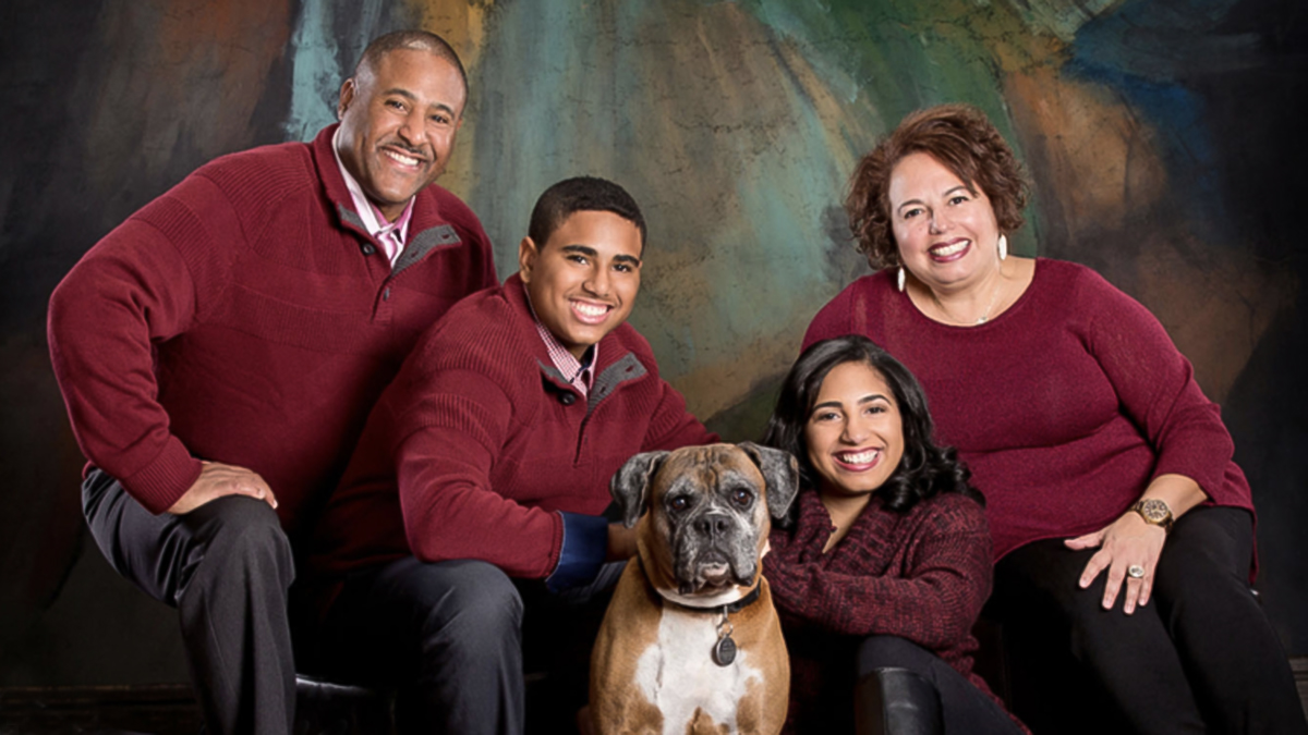 Family in maroon sweaters posing with their dog in a portrait studio