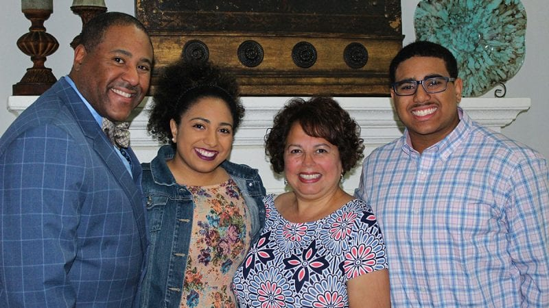 Family of four smiling in a group