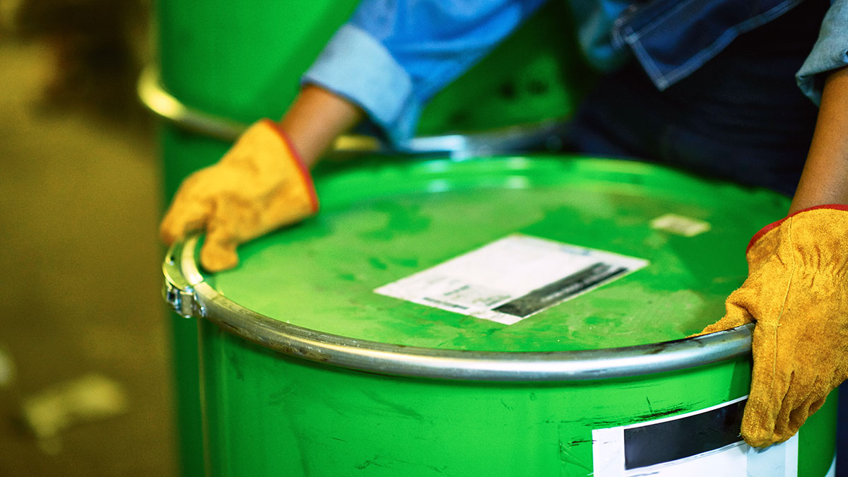 Gloved hands picking up a heavy green drum