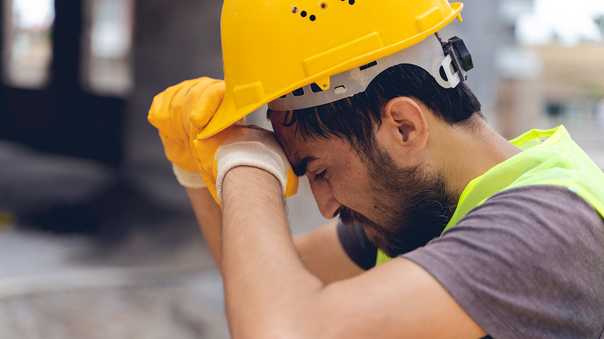 Young construction worker tipping back his hard hat and wiping sweat from his brow.