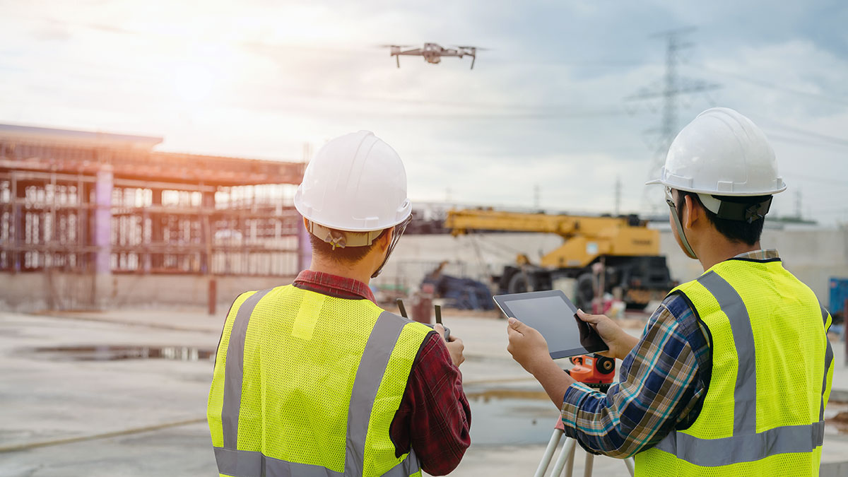 Two construction workers watch as drone hovers above job site in the distance.