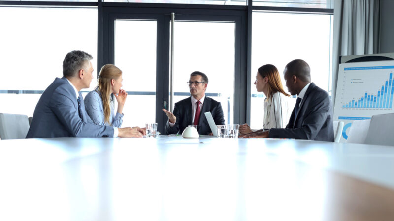 Multi-ethnic business people having discussion at table in board room