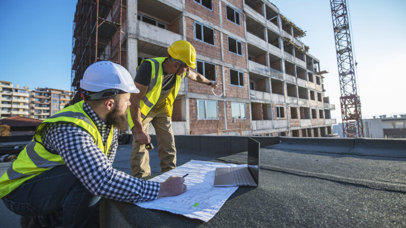 Architects on construction site reviewing architectural plans, blueprints.